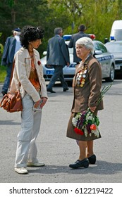 Volgograd, Russia - May 09, 2009: Woman and World War II veteran speak to each other on Victory Day celebration on the Mamaev Kurgan in Volgograd