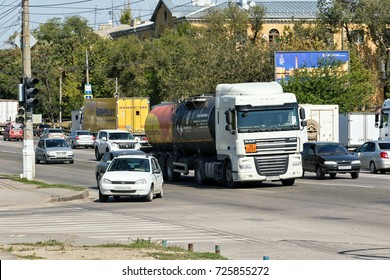 VOLGOGRAD - SEPTEMBER 8: A truck with a tank for transportation of petroleum products stands at the traffic lights with public transport. September 8, 2017 in Volgograd, Russia.