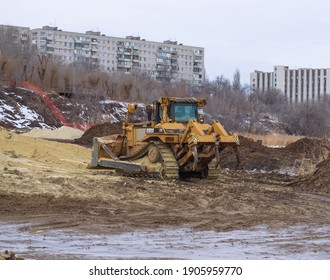 Volgograd, Volga bank, Russia, January 30, 2021. Powerful bulldozer on excavation works to strengthen the river bank.