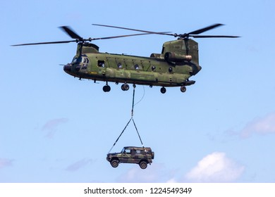 VOLKEL, THE NETHERLANDS - JUN 15, 2013: Royal Netherlands Air Force Boeing CH-47 Chinook transport helicopter with a slingload in flight.