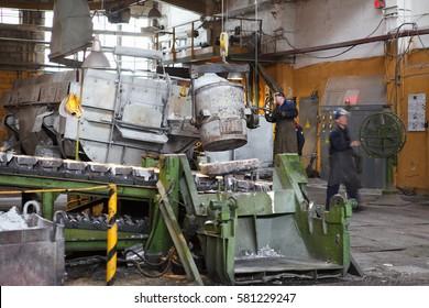 VOLKHOV, RUSSIA - CIRCA MAR, 2012: Metallurgists smelt liquid aluminum from pot in ingot making machine in workshop of factory. Volkhovsky Aluminium Smelter is located near St. Petersburg
