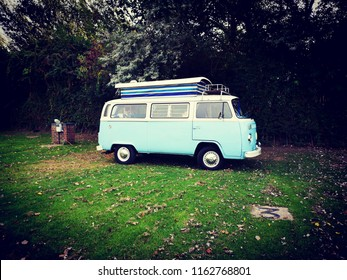 Volkswagen Camper - 23rd August 2018 - Selsey, West Sussex, United Kingdom. VW Campervan in retro light blue. Side view of Camper on campsite. Pop up striped roof snd shiny metal hub caps. Luggage.