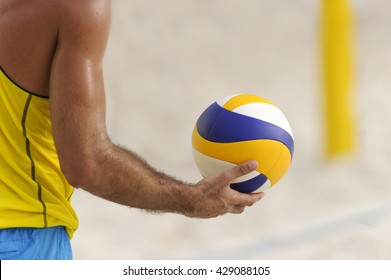 Volleyball beach player is a male athlete getting ready to serve the volleyball at the beach.
