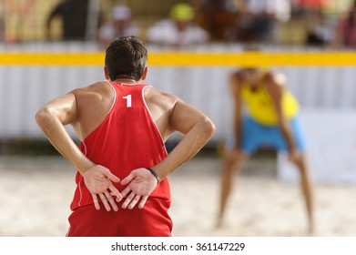 Volleyball beach player is a male volleyball player giving signals to his partner as his opponent waits for the serve on the beach.