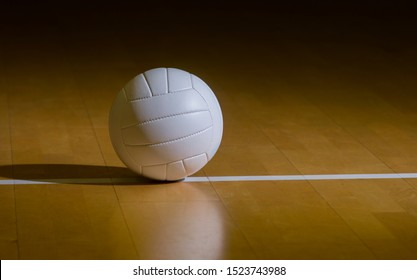 Volleyball court wooden floor with ball on black with copy-space