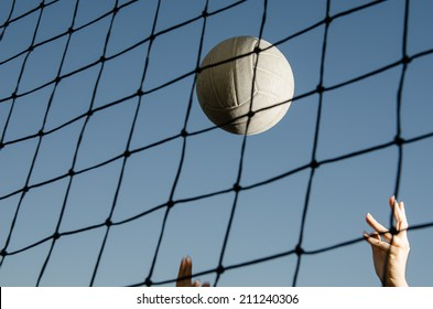 Volleyball flying through air with hands visible