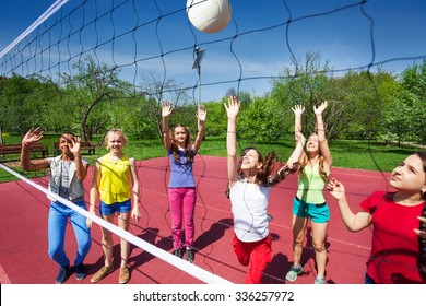 Volleyball game with playing teenage children on the playground during summer sunny day