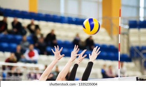 Volleyball players ' hands are above the volleyball net