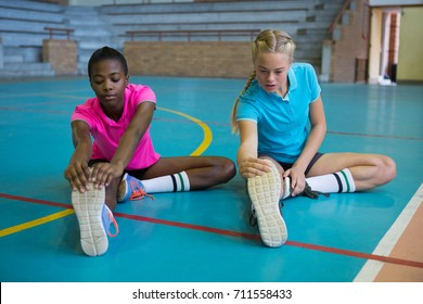 Volleyball players performing stretching exercise in court