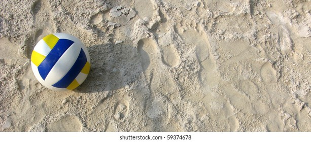 Volleyball yellow and blue in the sand