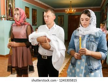 Volodymyr, Volyn / Ukraine - September 09 2018: Godfather hold newborn baby during the christening ceremony at orthodox church
