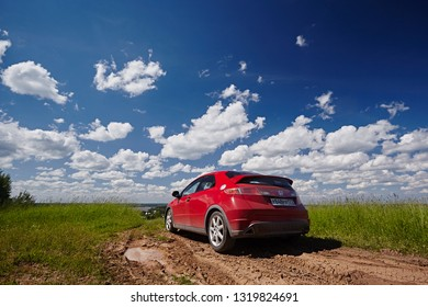 Vologda Region, Russia - May 2017:  A red car Honda Civic is driving along a dirt road amidst fields against a blue sky and green grass.