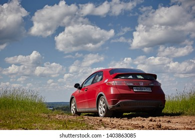 Vologda Region, Russia - May 2017:  A red car Honda Civic is driving along a dirt road amidst fields against a blue sky and green grass. Back view