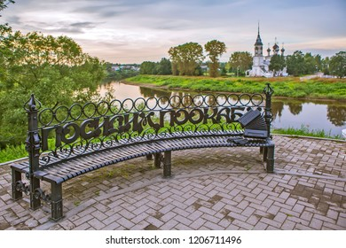 """VOLOGDA, RUSSIA - AUGUST 03, 2018: Photo of Evening landscape. Forged bench with the words """"Let's sit and water"""" on the embankment of the river Vologda and the view of the Church of the Presentation o"""