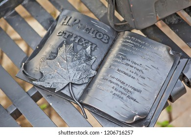 """VOLOGDA, RUSSIA - AUGUST 03, 2018: Photo of The book of poems by N. Rubtsov. Fragment of a bench with the words """"Let's sit and drink"""" on the embankment of the river Vologda."""