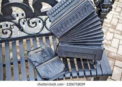 """VOLOGDA, RUSSIA - AUGUST 03, 2018: Photo of Book of poems by N. Rubtsov and accordion. Fragment of a bench with the words """"Let's sit and drink"""" on the embankment of the river Vologda."""
