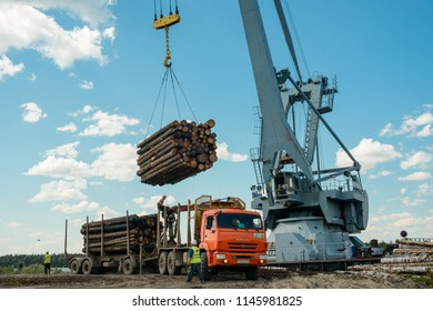 Vologda, Russia - july 17, 2018: Industrial cargo crane unloading timber from the truck. Logging, transportation of wood.