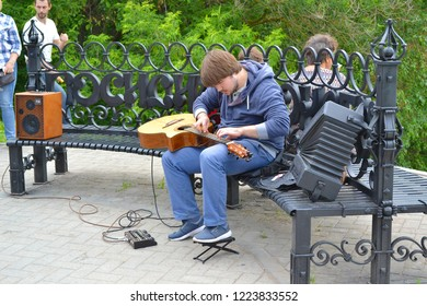 Vologda, Russia - June 30, 2018: On the City Day holiday in Vologda, on the embankment of the river Vologda, a street musician plays the guitar in an unusual way, putting the guitar on his knees.