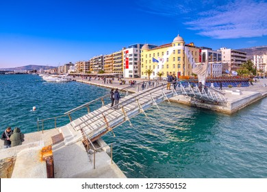 Volos, Greece – January 02, 2018: Building of the university at the seafront of Volos city with a copy of Jason's ancient trireme.
