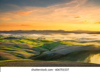 Volterra foggy panorama, rolling hills and green fields on sunset. Tuscany Italy, Europe