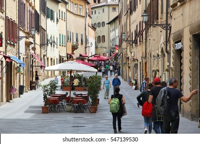 VOLTERRA, ITALY - MAY 4, 2014: People walk in medieval Old Town of Volterra, Tuscany, Italy. Tuscany has 43.4 million annual visitors (2014).