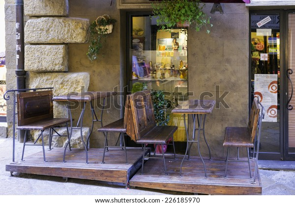 VOLTERRA, ITALY/PISA - AUGUST 4: External view of a typical tuscan winery shop in Volterra; in the foreground, two empty tables waiting for client. Volterra, Italy - August 4, 2014