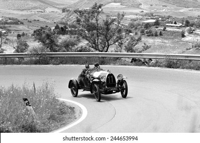 VOLTERRA (PI), ITALY - MAY 17: A Bugatti T23 Brescia takes part to the 1000 Miglia classic car race on May 17, 2014 near Volterra (PI). The car was built in 1923. Black and white image.