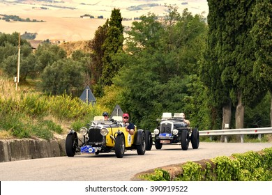 VOLTERRA (PI), ITALY - SEPTEMBER 19: A yellow Aston Martin and a black Wolseley Hornet Special take part in the GP Nuvolari classic race on September 19, 2015 near Volterra. Both were built in 1933.