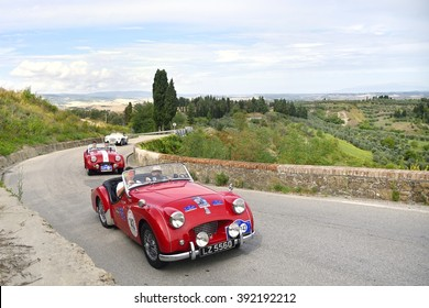 VOLTERRA  (PI), ITALY - SEPTEMBER 19: Two red Triumph TR2 sport, followed by an A-H, take part in the GP Nuvolari on September 19, 2015 near Volterra (PI). The Triumphs were built in 1954 and 1955.