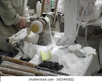Volterra, Tuscany, Italy, May 23, 2019. Artisan craftsman carving alabaster on a lathe.  Workshop / studio adjacent to Porta Marcoli.  Volterra, Tuscany, Italy, May 23, 2019