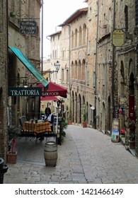 Volterra, Tuscany, Italy, May 23, 2019.  Street scene with restaurant near Piazza dei Priori.  One person in shot.  Volterra, Tuscany, Italy, May 23, 2019.