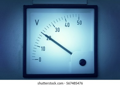 Voltmeter on the white wall in blue light. Toned