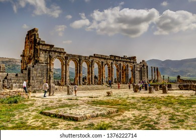 Volubilis, Morocco - March 25, 2019: People walking amongst the ancient ruins of Volubilis, Morocco.