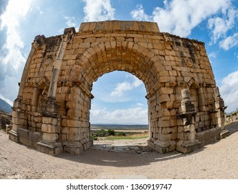 """Volubilis. Morocco - October 14, 2018: Full view of """"The Arch of Caracalla"""", shot with an 8mm fish-eye lens."""