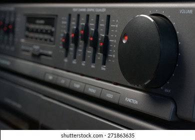 Volume and graphic equalizer controls on an audio system shot with low key light and selective focus