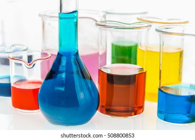 volumetric flask and various beakers with different types of indicators in acids and basis, four colors of indicators in several solutions