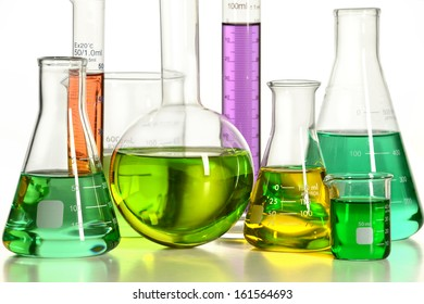 Volumetric laboratory glassware over white background with reflections on table