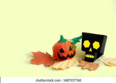 Volumetric paper skull and Jack-o-lantern with autumn leaves on yellow background. Paper art and craft. Festive Halloween concept. Copy space