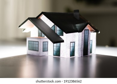 Volumetric project of house. Layout of a house with an open roof. Miniature layout of a cottage top view. Building model as a symbol of architectural business. Design in architectural bureau.