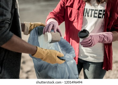 Voluntary action. Close up of boy and girl wearing gloves participating in voluntary cleaning action on the beach together
