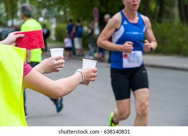 Voluntary assistants are handing water refreshments to runners
