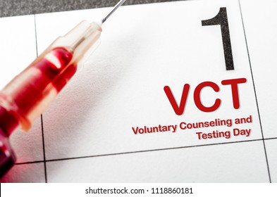 Voluntary counseling and testing day with blood in tube and syringe on calendar.