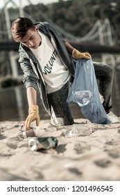 Voluntary work. Young handsome student wearing yellow gloves providing voluntary work while gathering garbage on beach