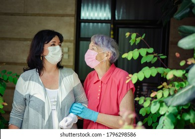 A volunteer or advanced physiotherapist walks a lonely old woman several times a week. As it should be in the Coronavirus epidemic, both put on protective face masks and gloves.