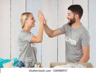 Volunteer couple giving high five to each other against wooden background