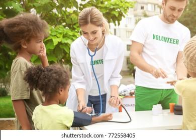 Volunteer doctor measuring blood pressure of poor African child outdoors