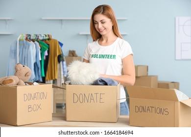 Volunteer with donations for poor people indoors