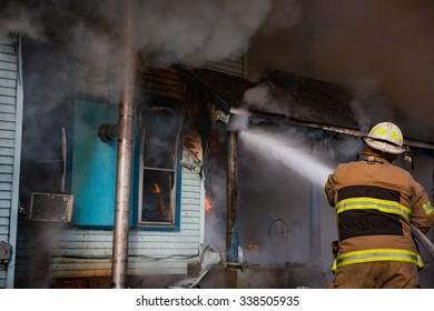 volunteer firefighter spraying water on house