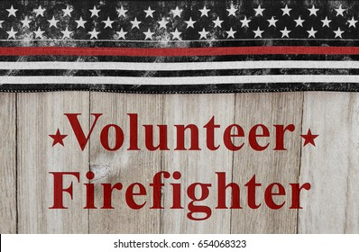 Volunteer Firefighter text with USA patriotic old thin red line flag on a weathered wood