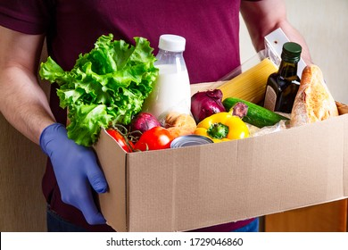 Volunteer in gloves holding food in a donation cardboard box with various food. Open cardboard box with oil, vegetables, milk, canned food, cereals and pasta. Food delivery concept with copy space.